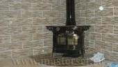 коричневая печка vc defiant установлена на угловой подиум в отделке керамической плиткой