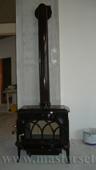 печка jotul f500 brm в коричневой эмали, коричневая труба заведена в дымоходный канал в стене