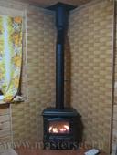 печка нордика изетта установлена на подиум в плитке, угол стены за печью защищен экраном в плитке