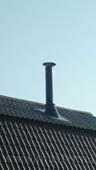 печная труба в цвет крыши проходит в пологом скате кровли